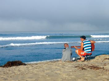 tourists playing guitar and watching the waves at Alentejo Surf Camp